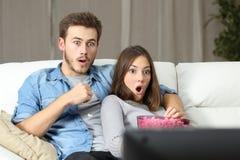Hållande ögonen på tv för häpna par hemma Royaltyfria Foton