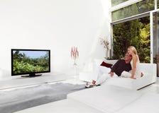 Hållande ögonen på TV för härliga par Arkivfoton