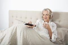 Hållande ögonen på TV för hög kvinna, medan ha kaffe i säng Royaltyfria Bilder