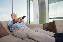 Hållande ögonen på TV för hög man på soffan hemma Royaltyfria Bilder