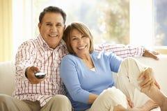 Hållande ögonen på TV för höga latinamerikanska par hemma arkivbilder