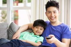 Hållande ögonen på TV för kinesisk familj på sofaen tillsammans Arkivbild