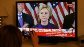 Hållande ögonen på TV för kvinna efter USA-val som lyssnar till Hillary Clinton anförande stock video