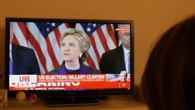 Hållande ögonen på TV för kvinna efter USA-val som lyssnar till Hillary Clinton anförande lager videofilmer