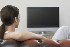 Hållande ögonen på TV för kvinna i vardagsrum Arkivbild