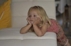 Hållande ögonen på TV för liten flicka som ligger på soffan royaltyfria foton