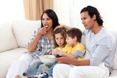 Hållande ögonen på TV för livlig familj och ätachiper Arkivbild