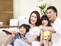 Hållande ögonen på TV för lycklig asiatisk familj hemma royaltyfri foto