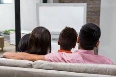 Hållande ögonen på tv för lycklig familj på soffan royaltyfria bilder