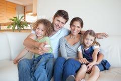 Hållande ögonen på TV för lycklig familj tillsammans Arkivbild