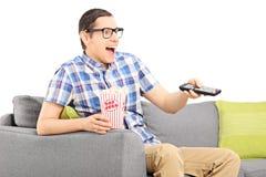 Hållande ögonen på TV för lycklig man och ätapopcorn Royaltyfri Foto