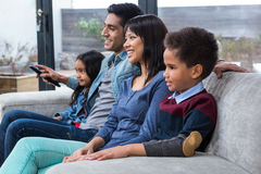 Hållande ögonen på tv för lycklig ung familj royaltyfri bild