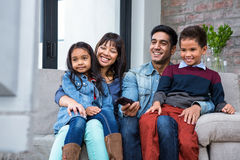 Hållande ögonen på tv för lycklig ung familj Royaltyfri Fotografi