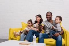 hållande ögonen på tv för lycklig ung familj tillsammans royaltyfri fotografi