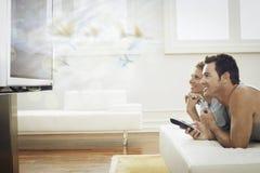 Hållande ögonen på TV för lyckliga barnpar hemma Arkivfoton