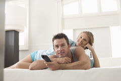 Hållande ögonen på TV för lyckliga par hemma Royaltyfri Foto
