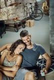 Hållande ögonen på TV för lyckliga par hemma royaltyfria bilder