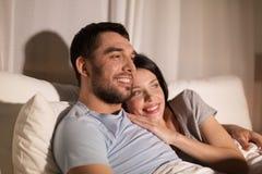 Hållande ögonen på tv för lyckliga par i säng på natten hemma Royaltyfri Fotografi