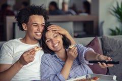 Hållande ögonen på tv för lyckliga par, medan äta pizza Grunt djup av fältet, fokus på mannen royaltyfri bild