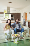 Hållande ögonen på tv för lyckliga par tillsammans Royaltyfri Foto
