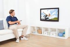 Hållande ögonen på TV för man i vardagsrum Royaltyfri Bild