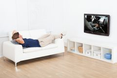 Hållande ögonen på tv för man, medan ligga på soffan Royaltyfria Bilder