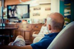 Hållande ögonen på tv för mellersta ålderman fotografering för bildbyråer