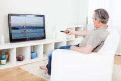 Hållande ögonen på tv för mogen man Arkivbild