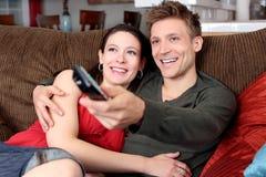 Hållande ögonen på TV för par Royaltyfri Fotografi