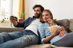 Hållande ögonen på TV för par på en soffa hemma arkivbild