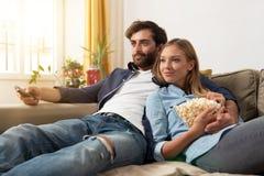 Hållande ögonen på TV för par på en soffa hemma arkivfoto