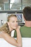 Hållande ögonen på TV för par hemma Royaltyfri Fotografi