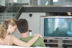 Hållande ögonen på TV för par hemma Arkivfoto