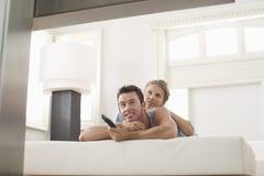 Hållande ögonen på TV för par hemma Fotografering för Bildbyråer
