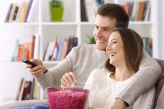 Hållande ögonen på tv för par hemma i vinter Royaltyfri Bild