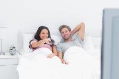 Hållande ögonen på tv för par i deras säng Royaltyfri Foto