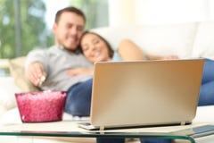 Hållande ögonen på tv för par i en bärbar dator hemma Royaltyfri Foto