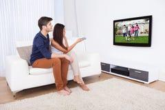 Hållande ögonen på TV för par i vardagsrum Royaltyfri Fotografi