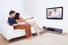 Hållande ögonen på TV för par i vardagsrum Royaltyfria Bilder