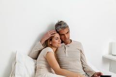 Hållande ögonen på TV för par på sängen Royaltyfria Bilder