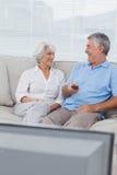 Hållande ögonen på tv för par på soffan Arkivbilder
