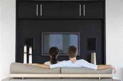 Hållande ögonen på TV för par tillsammans i vardagsrum Arkivfoton