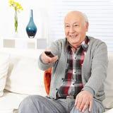 Hållande ögonen på TV för pensionärman Arkivbilder