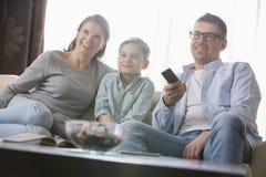Hållande ögonen på TV för pojke med föräldrar i vardagsrum Royaltyfri Fotografi