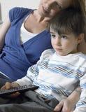 Hållande ögonen på TV för pojke och för moder hemma Arkivbilder