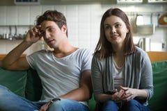 Hållande ögonen på tv för roliga par som hemma sitter på soffan arkivbilder