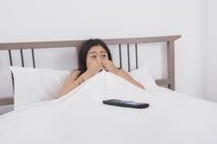 Hållande ögonen på TV för skrämd kvinna i säng Arkivbild