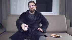 Hållande ögonen på tv för stilig skäggig man stock video