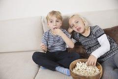 Hållande ögonen på TV för syskongrupp och ätapopcorn Arkivfoto