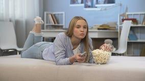 Hållande ögonen på tv för tonårs- flicka i rum med fjärrkontroll, i hand och att äta pophavre stock video